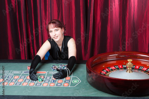 Plakat  girl wearing  black gloves and black dress parlays in a casino, ludomania