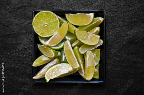 Staande foto Vlees Green Lime in Plate Placed on Black Stone Background Surface
