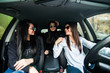 Just keep driving. Three beautiful young cheerful women looking away with smile while sitting in car