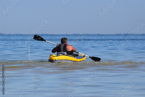 Poster Water Motor sports Man rowing in inflatable kayak in the sea.