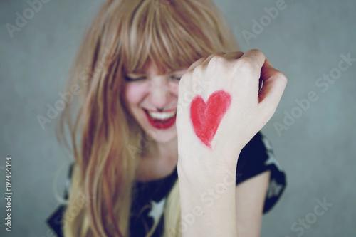 Fotografía  Chica joven con un corazón rojo pintado en su mano