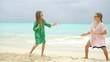 Adorable little girls having a lot of fun at tropical beach playing together background turquiose water and blue sky