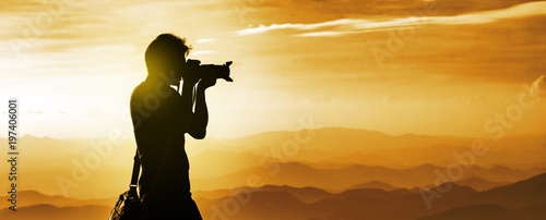 Miel Silhouette of a backpacker photographer with mountains layer background during the sunset