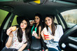 Enjoying their lunch in the car. Three beautiful young cheerful women looking at each other with smile and eating take out food while sitting in car