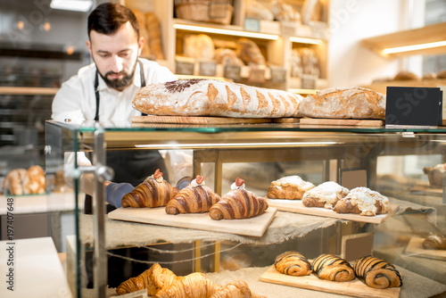 Stampa su Tela Seller putting delicious croissants on the store showcase of the bakery house