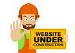 Serious worker man wearing hard hat holding banner with website under construction text showing stop gesture