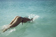 Young girl in bikini - dives underwater with fun under blue water of the lake. Beach swimming activity on summer