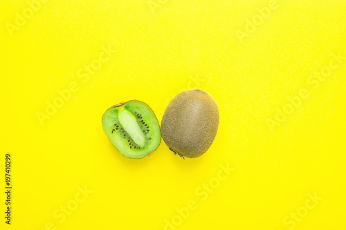 Ripe Juicy Whole and Halved Kiwi on Solid Yellow Background. Vitamins Healthy Diet Summer Detox Vegan Tropical Fruits Concept. Poster Banner Template. Copy Space Flat Lay