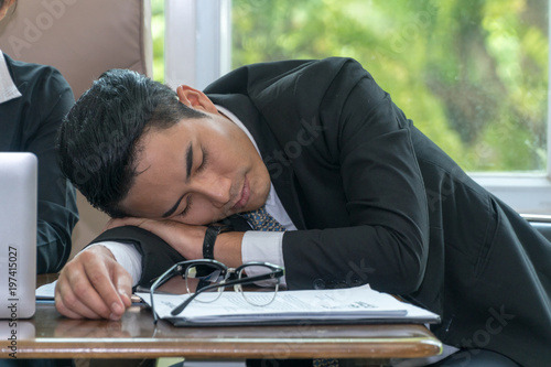 Fototapeta Young businessman leaning his head on desk and keeping eyes closed while sitting at his working place. obraz na płótnie