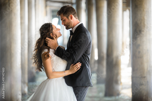 Photo Stunning artistic portrait of bride and groom in love embracing with gorgeous ba