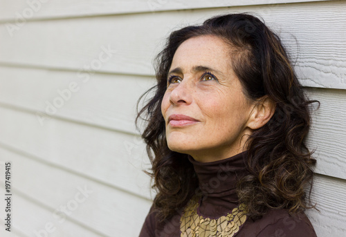 Fascinating mature woman with optimistic look leans on white wood plank wall background Wallpaper Mural