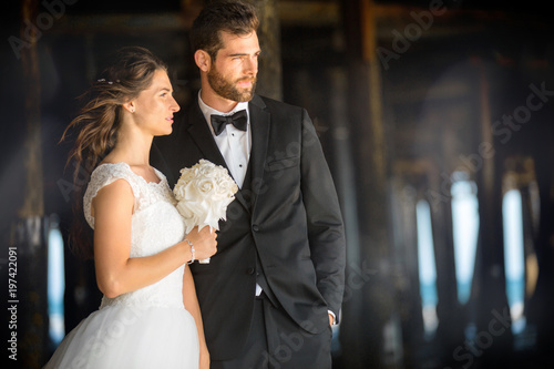 Canvas Beautiful portrait of bride and groom outdoors under ocean pier, classic and sty