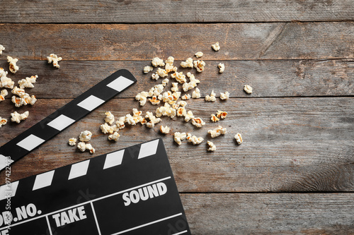 Fototapeta Clapperboard and popcorn on wooden background