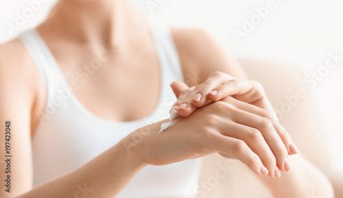Obraz na plátně Young woman applying body cream at home