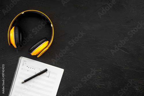 Fotografía  Work space of composer or dj with headphones and notes black background top view