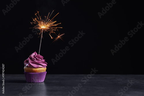 Delicious birthday cupcake with sparkler on table against black background Wallpaper Mural