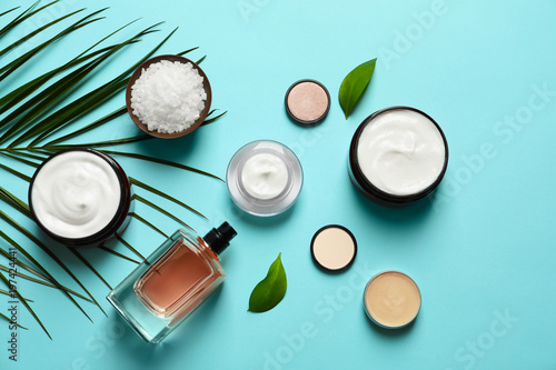 Fototapeta Different skin care cosmetic products with green leaves on color background, top view obraz na płótnie