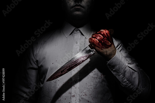Photo of a killer in white shirt holding a bloody knife on black background with upper lighting Canvas Print