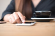 Closeup image of a woman using and touching smart phone on wooden table