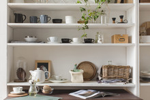 White Wooden Shelves With Decorative Elements And Elegant Kitchenware.
