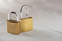 Two Padlock, Lock And Unlock, With Silvered Keys On White Wooden Background. Estate And Security Concept With Symbol Of Protection.