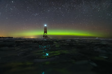 Wide Panoramic Night Sky View Of Milky Way And Beautiful Red And Green Aurora Borealis (northern Polar Lights) In Finland With Reflection On The Ice Floes On Frozen Lake With Lighthouse On The Shore