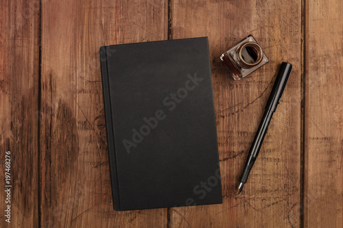 Fotografering  An overhead photo mockup of a black book with a fountain pen, an ink well, and a