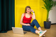 Attractive stylish girl with a laptop on a background of yellow wall.