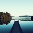 Picture of a minimalist blue landscape of a dock next to a beautiful calm lake. There are some leafy trees and hazy mountains in the the scene. The landscape is reflected on the water.