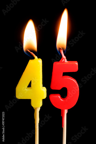Photographie  Burning candles in the form of 45 forty five figures (numbers, dates) for cake isolated on black background