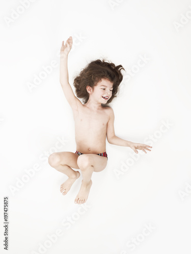 812457bd4d Smiling little boy in swimming trunks jumping with arms raised against a white  background