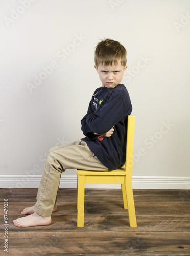 An Angry Little Boy Sits In A Yellow Time Out Chair On A Wooden