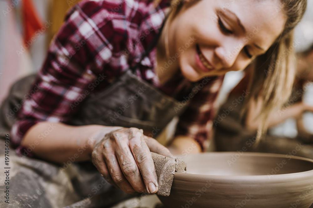 Fototapety, obrazy: Female potter making clay pottery on a spin wheel.