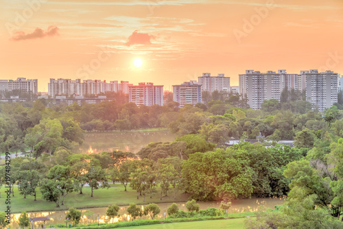 Public housing in Singapore. Aerial view sun setting behind row of lakeside apartments near a green urban park