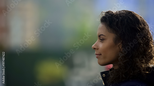 Fotografía  Inspired female model smiling, beautiful biracial young lady portrait in profile