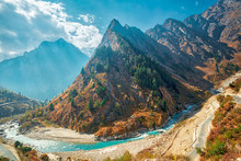 Himalayan Mountain Landscape With A Sharp Conical Wooded Mountain And Curving River And Road In The Foreground, The Himalayas, Uttarakhand Near Badrinath, India