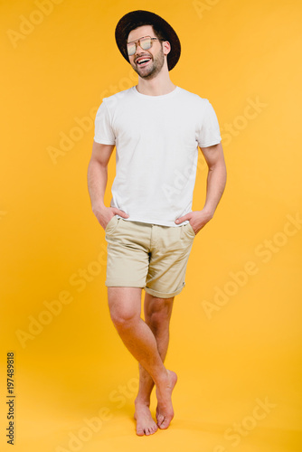 Valokuvatapetti young barefoot man in shorts and sunglasses standing with hands in pockets and l