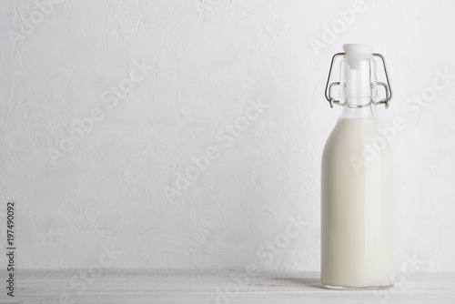Bottle of milk with vintage swing top lock, closed, on white wooden table with copy space