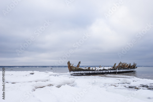 Old broken boat wreck and rocky beach in wintertime Poster