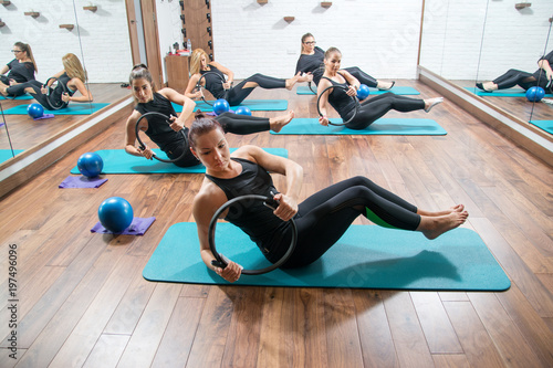 Photo  Attractive girls in sportswear training with pilates rings during exercise class