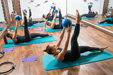 Sporty girls doing pilates exercises with fitness ball in gym