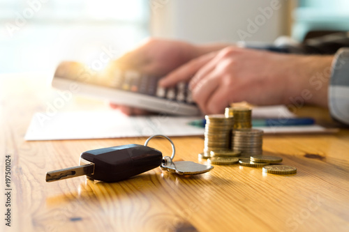 Fotografía  Car keys and money on table with man using calculator