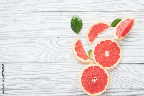 Valokuvatapetti Fresh red grapefruit and grapefruit slices on rustic white wooden table, top view, flat lay