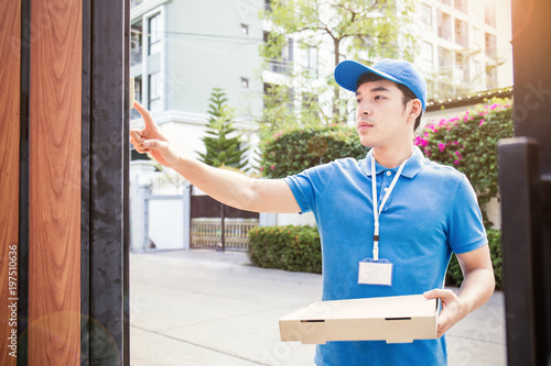Vászonkép Portrait of happy delivery asian man with blue uniform hands holding cardboard