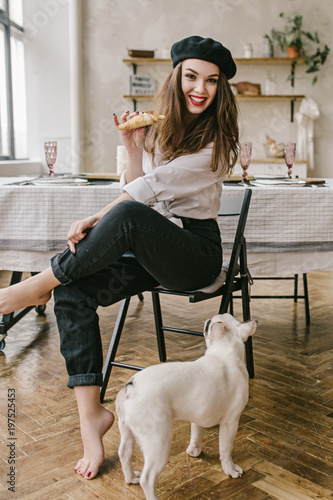 ae07080e24d6b Portrait of a happy smilling woman wearing black beret holding croissant  and french puppy cute bulldog
