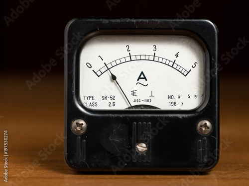 Photo An old black analog ampere meter on a wooden table