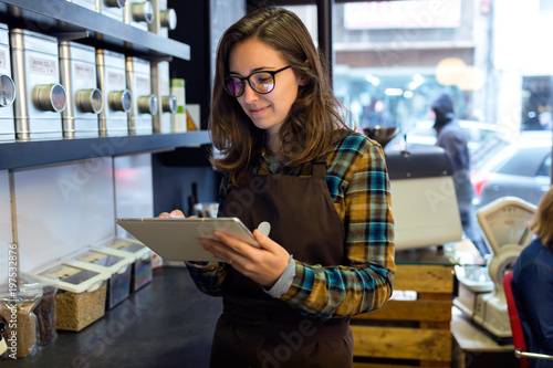 Fotografía Beautiful young saleswoman doing inventory in a retail store selling coffee