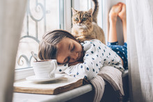 Child Relaxing With A Cat On A...