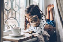 Child Relaxing With A Cat On A Window Sill