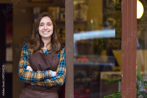 Canvas Print Beautiful young saleswoman looking at camera and leaning against the door frame of an organic store